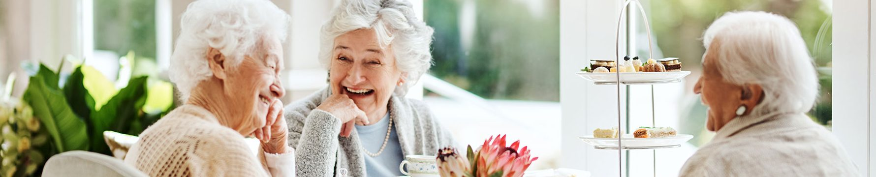 Three elderly women laughing while enjoying tea and pastries