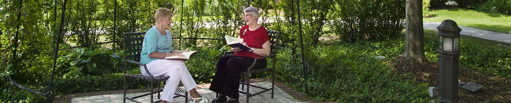 Two senior women sitting in the garden of their senior living community and reading books