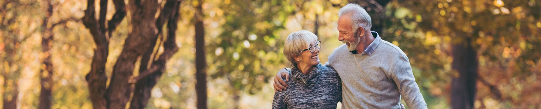 An elderly couple with their arms around one another walking on a trail in a park